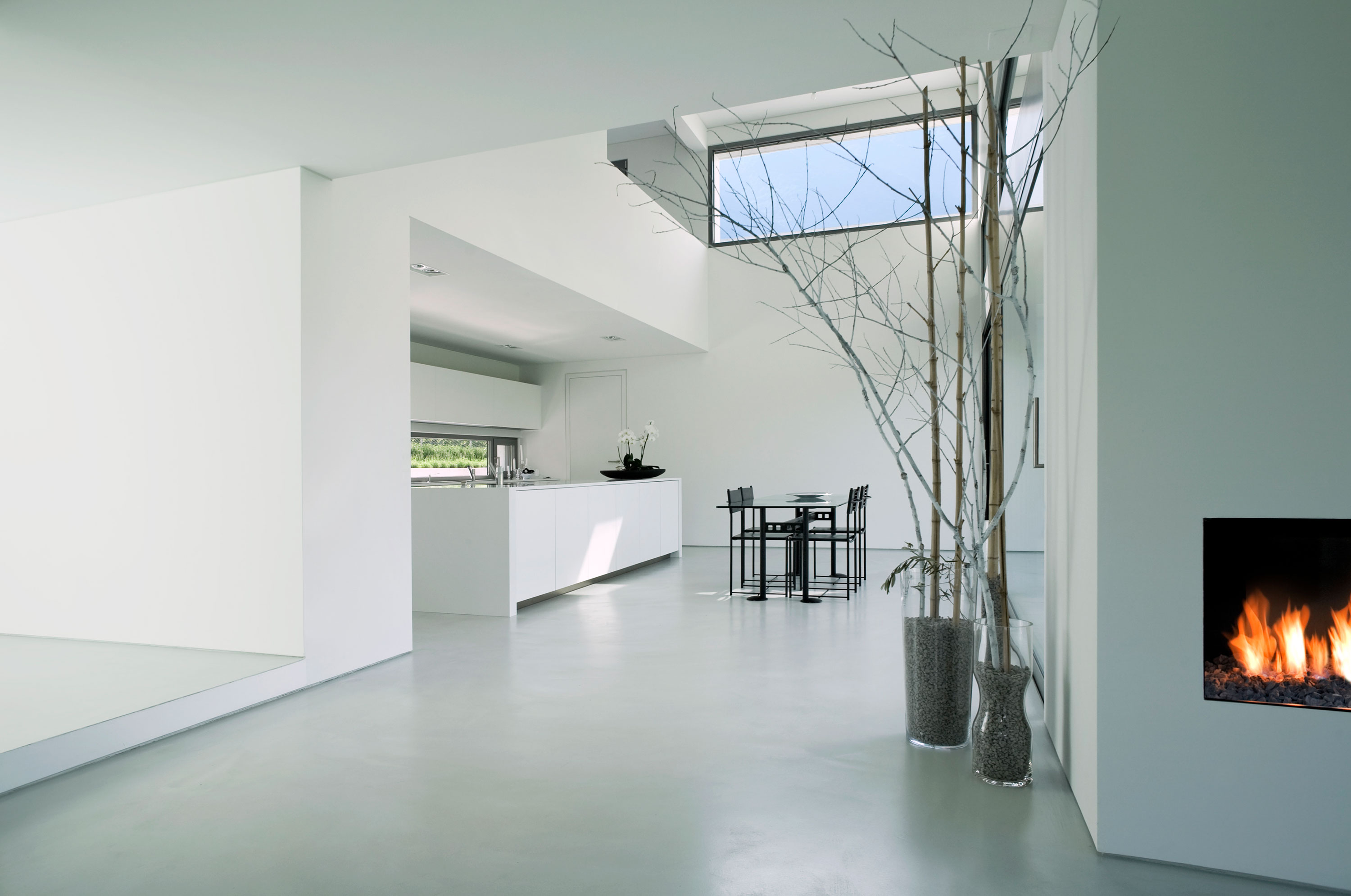 White space with small black dining area near kitchen with partial view of electric fireplace