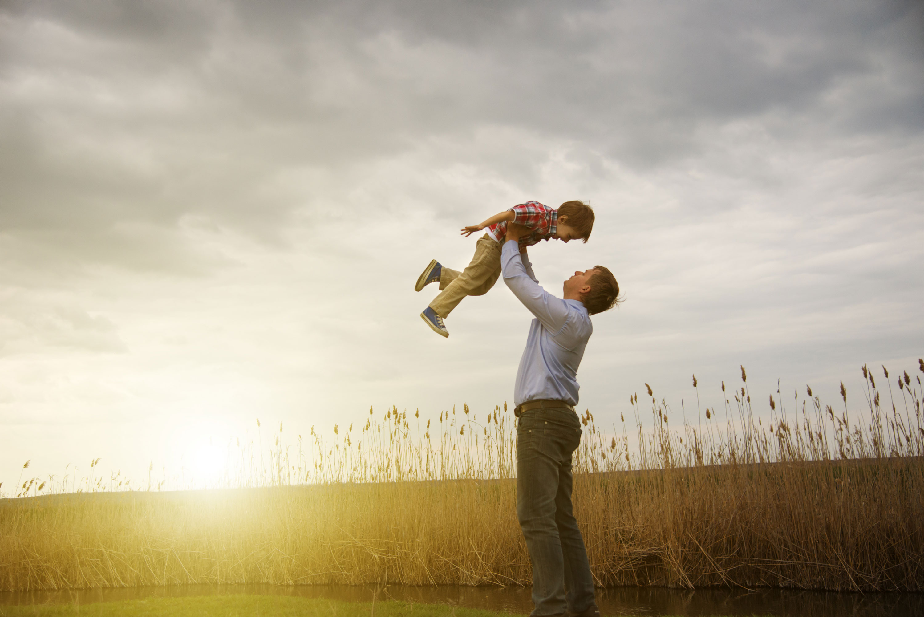 Man holding boy over his head in wheat field with sun shining