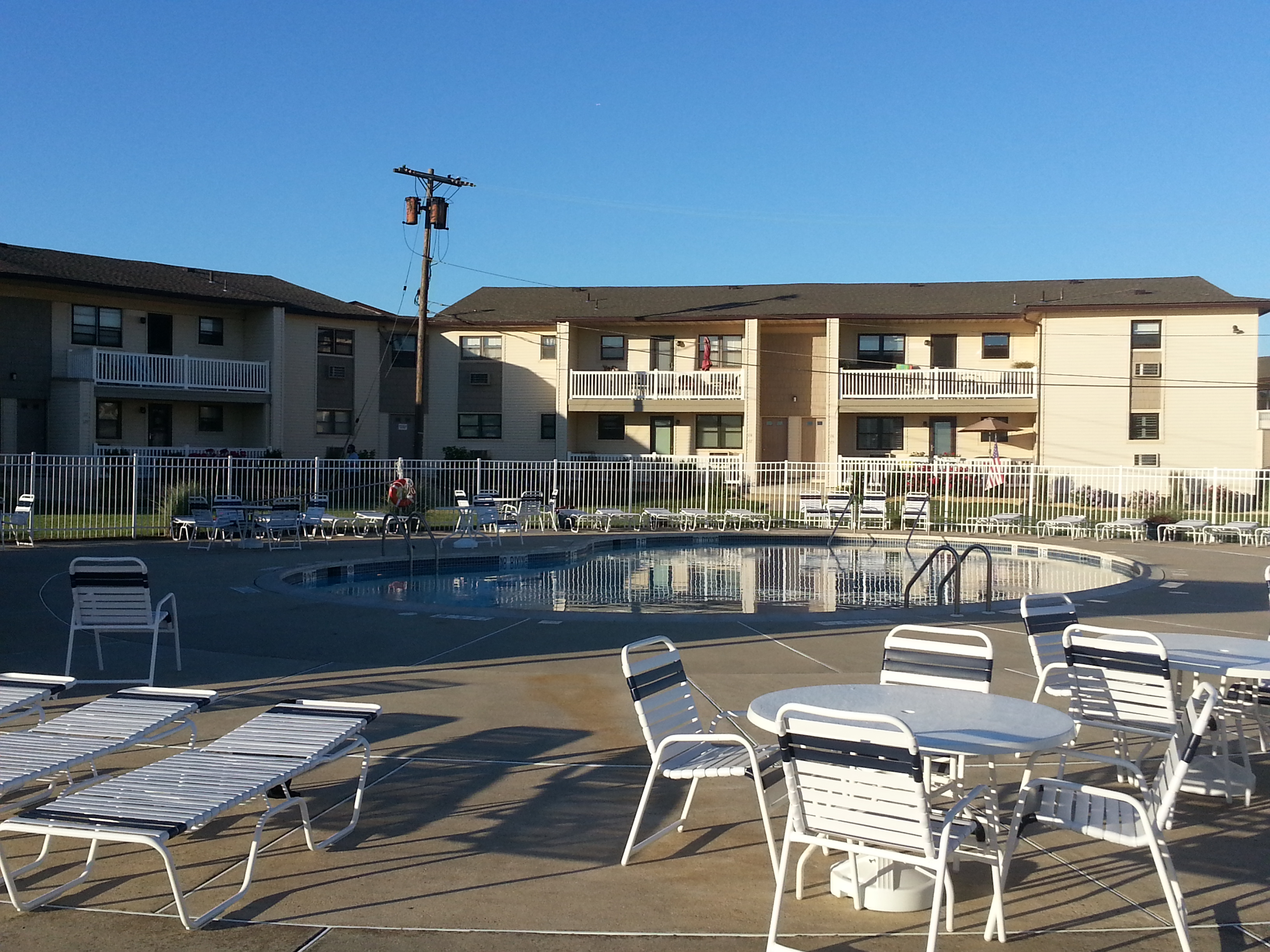 The Wharfside Manor community pool overlooks the river with a barbecue area next to it.